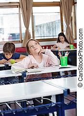 Schoolgirl Looking Up With Digital Tablet At Desk