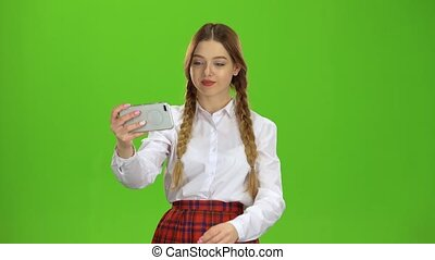 Schoolgirl makes a selfie. Green screen
