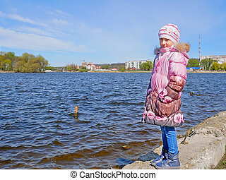 Schoolgirl on the dam in early spring