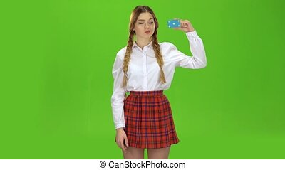 Schoolgirl picks up the card and points at it. Green screen...