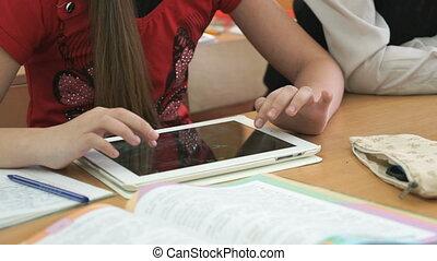 Schoolgirl plays in games using computer tablet