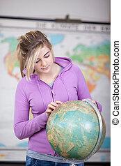 Schoolgirl pointing a place on a globe - Teenage schoolgirl ...