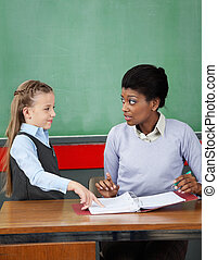 Schoolgirl Pointing In Binder While Teacher Looking At Her