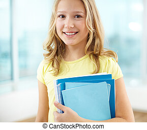 Schoolgirl - Portrait of cheerful schoolgirl with copybooks...