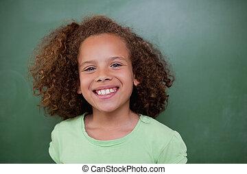 Schoolgirl posing in front of an empty chalkboard