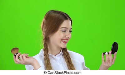 Schoolgirl powdered her nose with a brush. Green screen