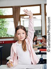 Schoolgirl Raising Hand While Standing In Classroom