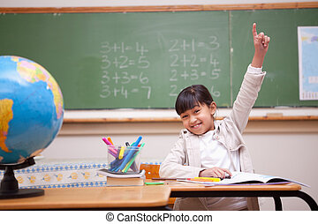 Schoolgirl raising her hand to answer a question