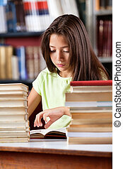 Schoolgirl Reading Book With Stack Of Books At Table