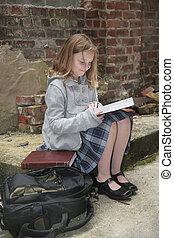 schoolgirl reading outside
