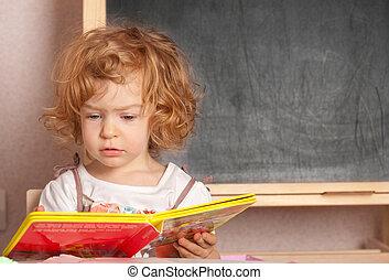 Schoolgirl reading textbook in a class against blackboard
