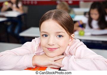 Schoolgirl Resting Chin On Hands In Classroom - Portrait of ...