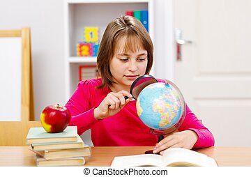 Schoolgirl searching with magnifier