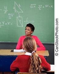 schoolgirl, sentando escrivaninha, com, professor, em, fundo