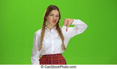 Schoolgirl shows her thumb down. Green screen