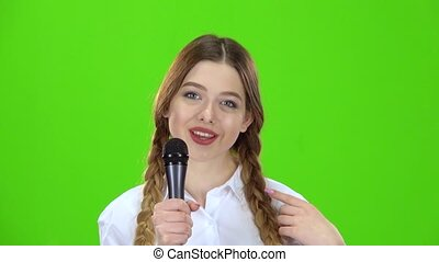 Schoolgirl sings into the microphone and smiles. Green...