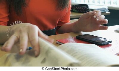 Schoolgirl sits at a desk, leafing through a book