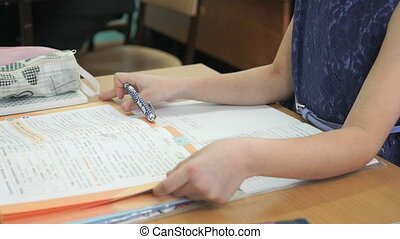 Schoolgirl sitting at desk flips pages of book