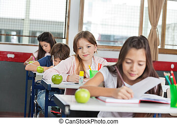 Schoolgirl Sitting At Desk With Classmates In A Row