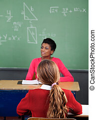 Schoolgirl Sitting At Desk With Teacher In Background