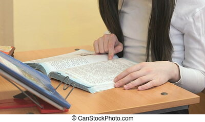 The schoolgirl sitting at the school desk reads textbook indoors