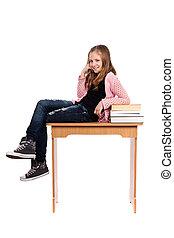 Schoolgirl sitting on desk with books