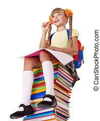 Schoolgirl sitting on pile of books.