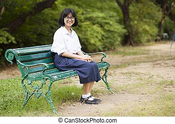 Schoolgirl. Sitting on the bench