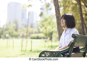 Schoolgirl sitting on the bench.