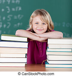 Schoolgirl smiling between two piles of books - Young...