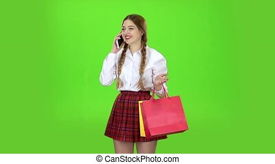 Schoolgirl speaks on the phone and holds shopping bags....