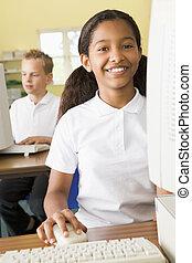 Schoolgirl studying in front of a school computer