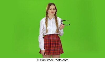 Schoolgirl takes off her glasses and yawns. Green screen - ...
