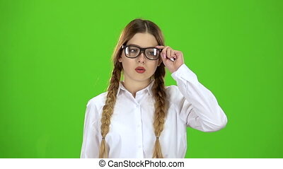 Schoolgirl takes off her glasses, she is tired. Green screen...