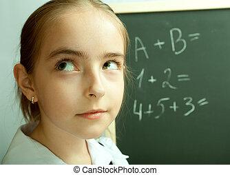 Schoolgirl thinking about exercises written on the blackboard