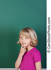 Schoolgirl thinking in front of the blackboard