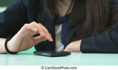 Schoolgirl typing text in smartphone. Close-up - Lesson at...