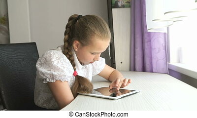 Schoolgirl uses a digital tablet computer at home