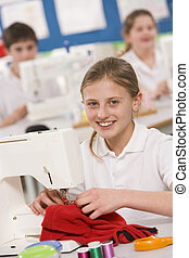 Schoolgirl using a sewing machine in sewing class