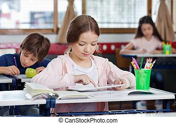 Schoolgirl Using Digital Tablet At Desk