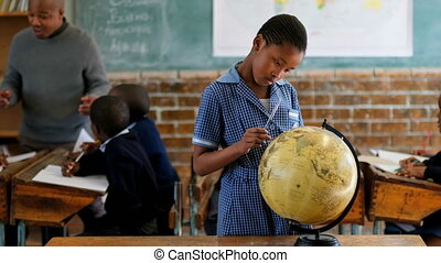 Schoolgirl using globe in classroom 4k - Schoolgirl using ...