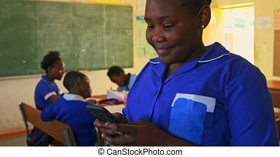 Schoolgirl using smartphone in classroom at a township school 4k