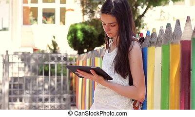 Schoolgirl using tablet pc in front of the school