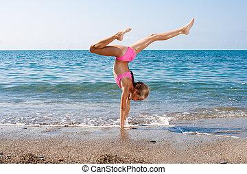 schoolgirl, vervaardiging, turnoefening, op, seashore
