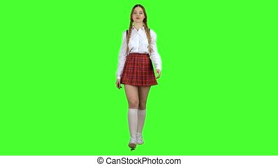 Schoolgirl walks with a backpack on her shoulders and waves her hand. Green screen