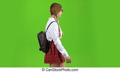 Schoolgirl walks with a backpack on her shoulders and waves her hand. Green screen. Side view
