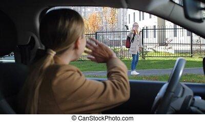 Schoolgirl waving goodbye to mother before school -...