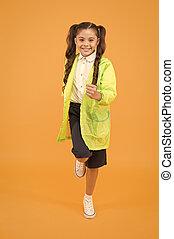 Schoolgirl wear raincoat. Schoolgirl wear water resistant clothes. Rainy day. Cute schoolgirl feel protected for spring weather. Waterproof concept. Kids raincoats with vibrant shapes unique designs