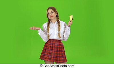 Schoolgirl with a credit card in her hands is sad. Green Screen