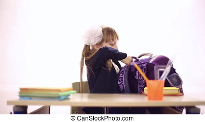 Schoolgirl with a huge backpack sitting at a school desk,...